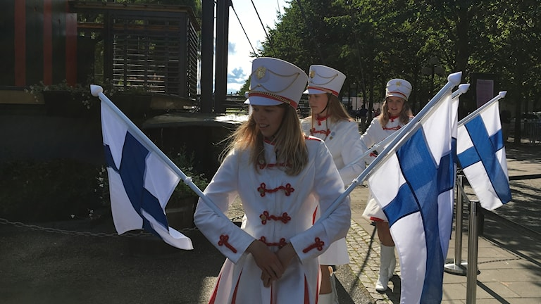 Girls in white uniform carrying Finnish flags