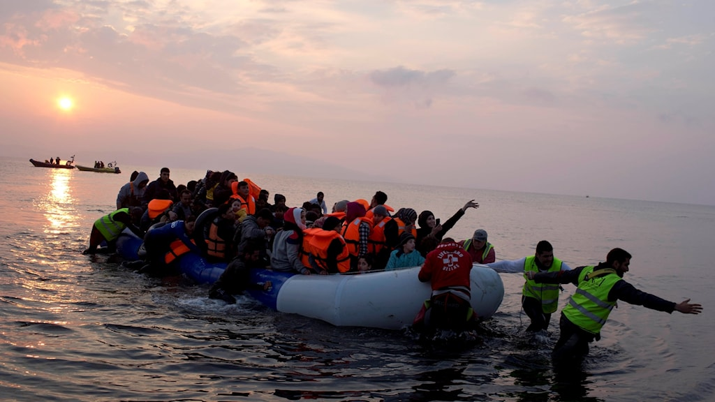 Volunteers help migrants and refugees on a dingy as they arrive at the shore of the northeastern Greek island of Lesbos, i March 2016.