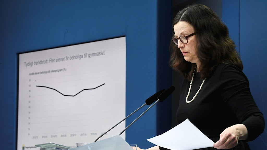 A picture of a woman with papers in front of a microphone.