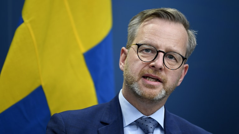 Home affairs minister Mikael Damberg in front of a Swedish flag, at the press conference.
