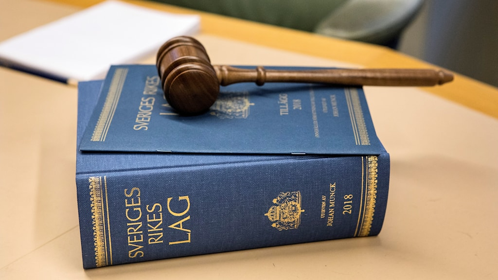 gavel resting on a thick book, bound in blue, with gold lettering