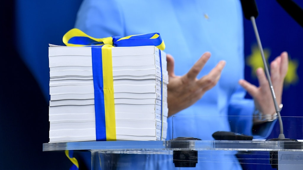 A stack of papers wrapped in yellow and blue ribbon.