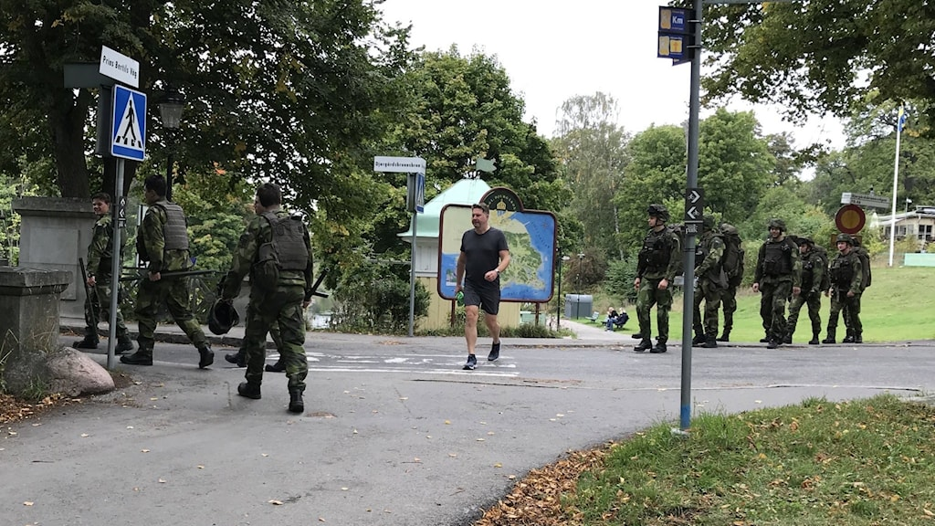 A group of soldiers leaves the path after taking their field-test, and another gorup arives, while a civilian jogger passes by.