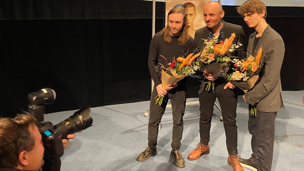Three people pose with bouquets while a photographer takes a picture of them.