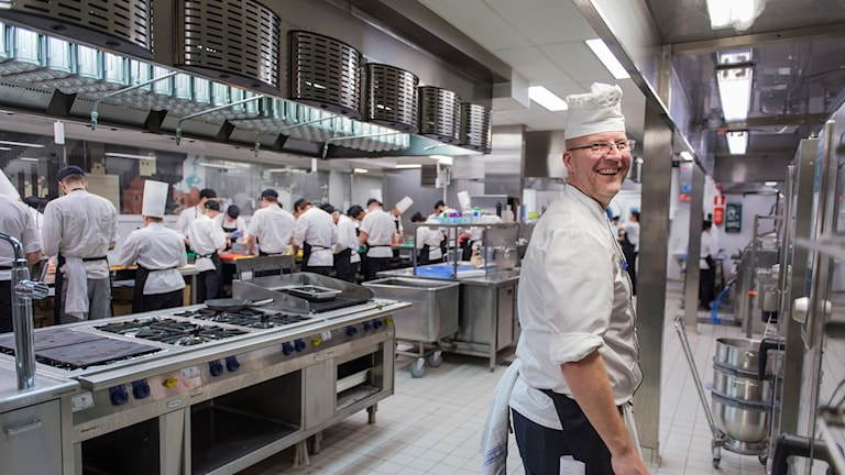 A chef inside a large kitchen.