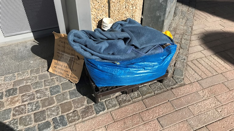 A makeshift seat for a beggar outside a shop