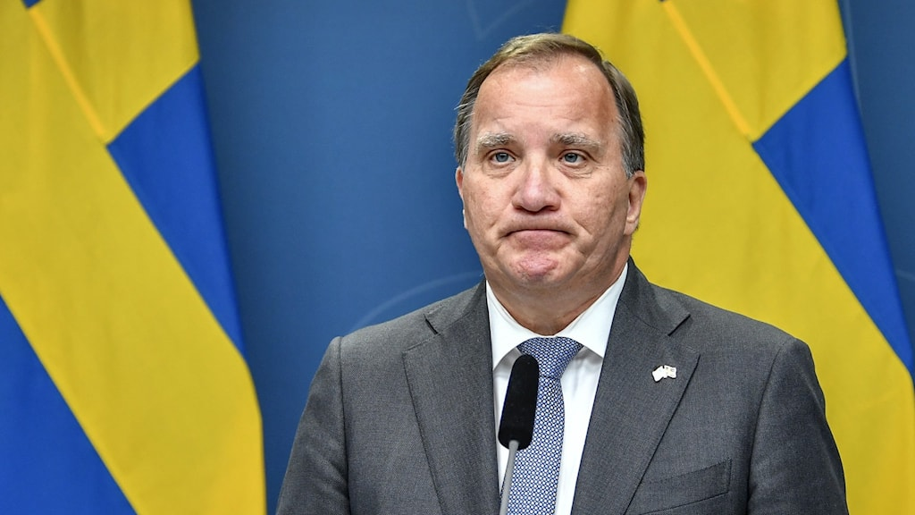 A man at a press conference frowning