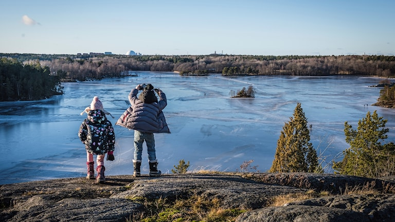 Two children looking out across a Swedish lake