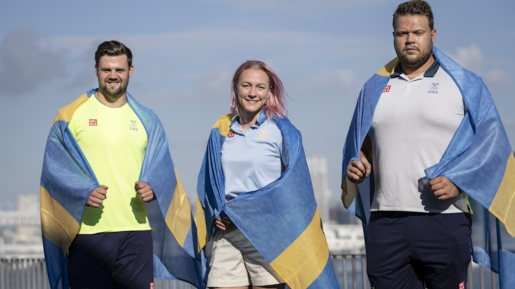 three people pose in summer attire with Swedish flags draped over their shoulders