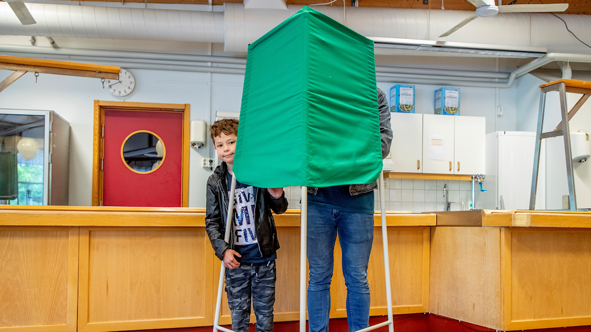A boy and a man behind a curtain, voting in the EU election.