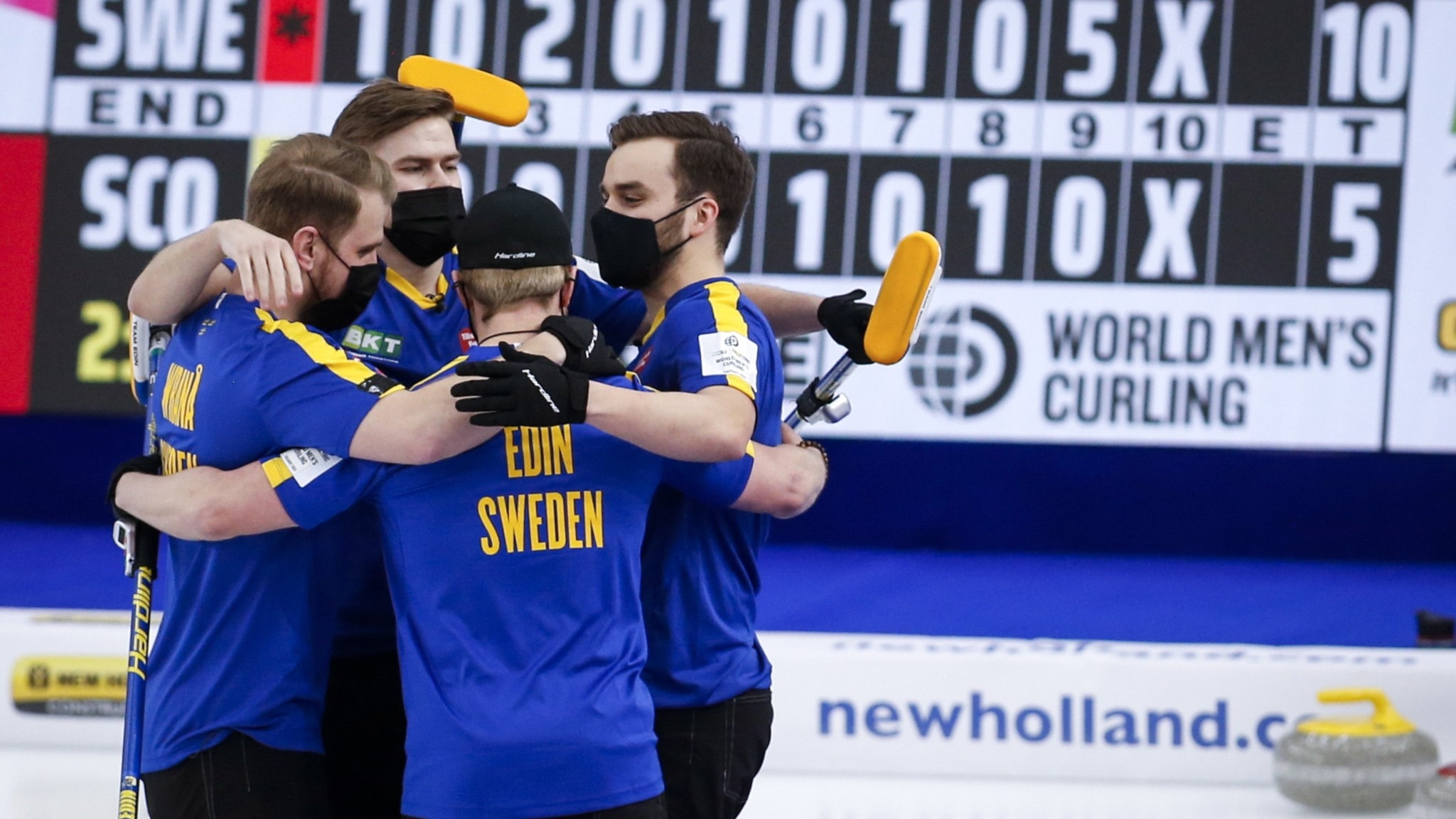 Four members of Sweden's men's team in curling, dressed in blue jerseys, celebrating with their arms around one another.