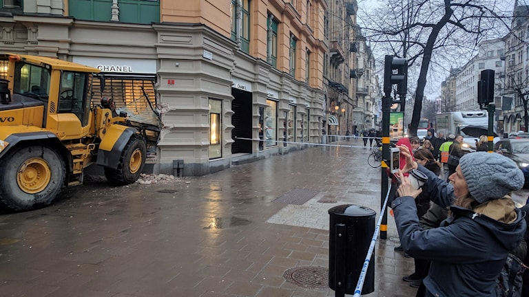 Stockholm commuters take pictures of a bulldozer rammed through the windows of Chanel.