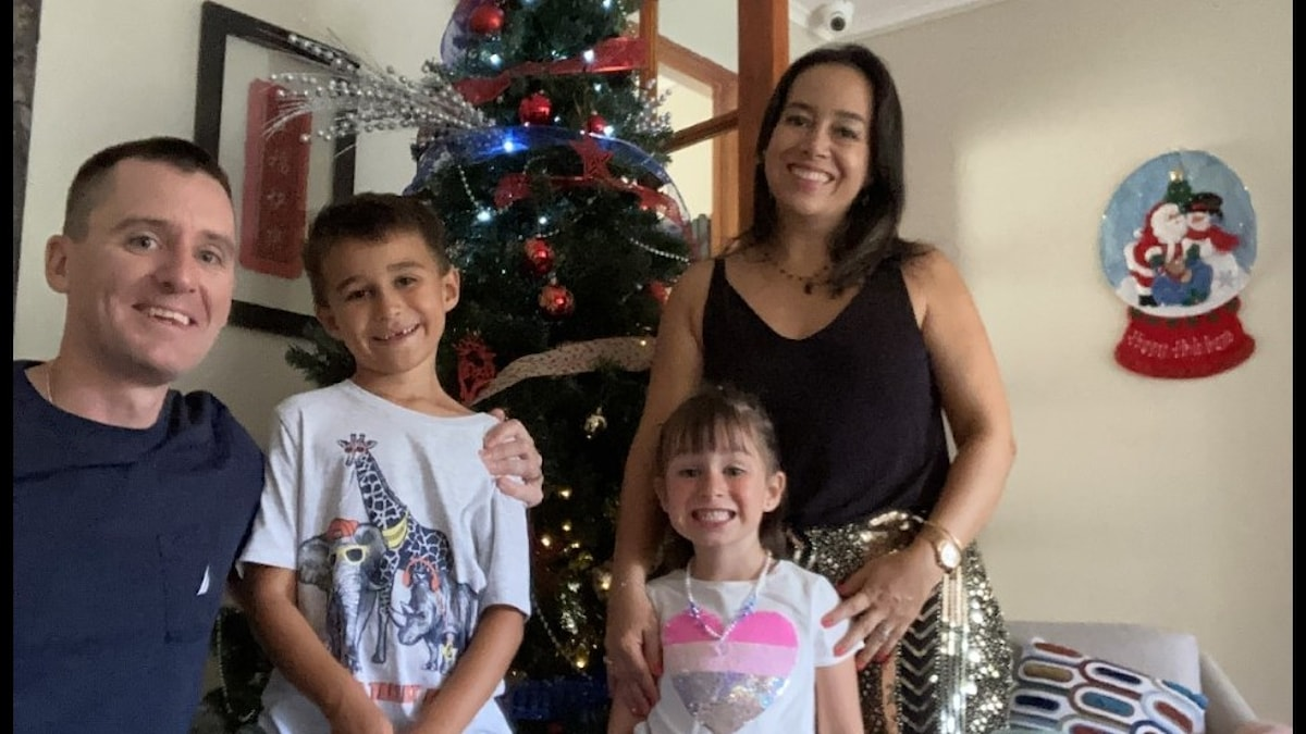 Man, woman and two children in front of a Christmas tree.