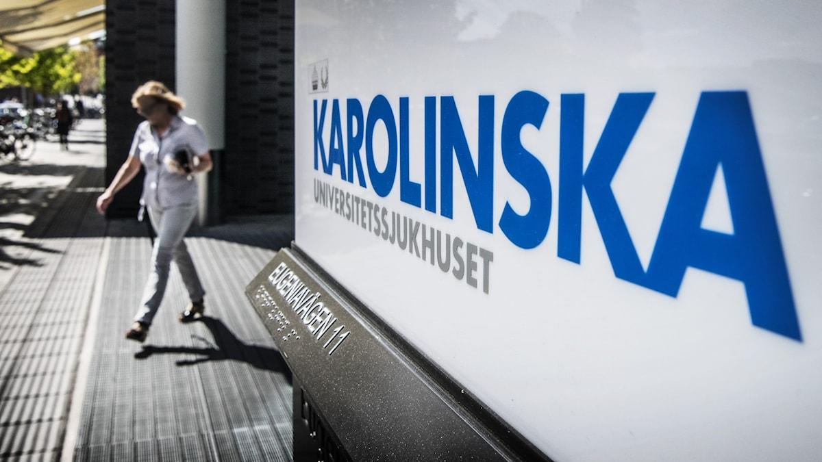 A woman walking outside of the Karolinska Hospital.