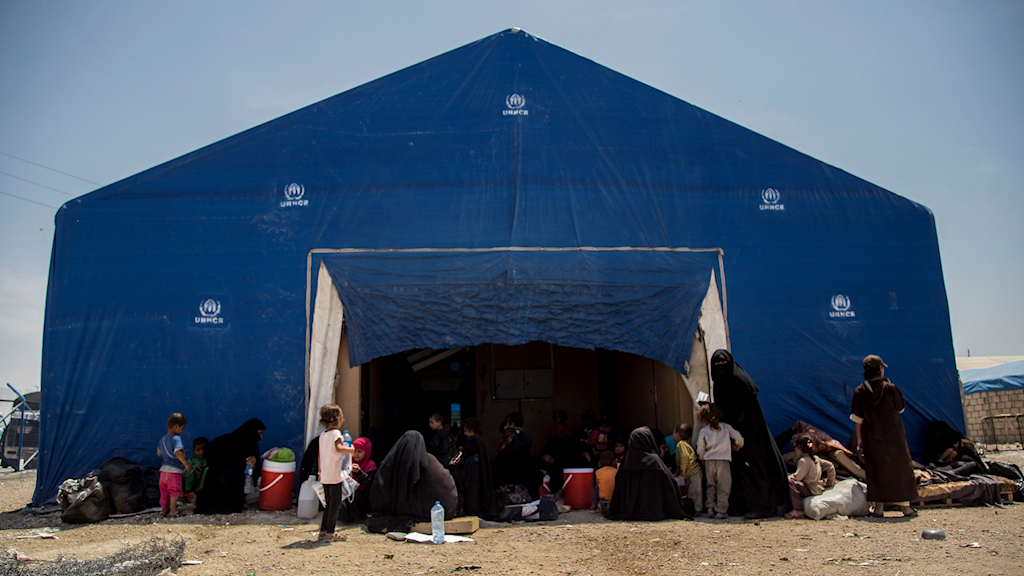 A large blue tent on arid ground, with women and children nearby.