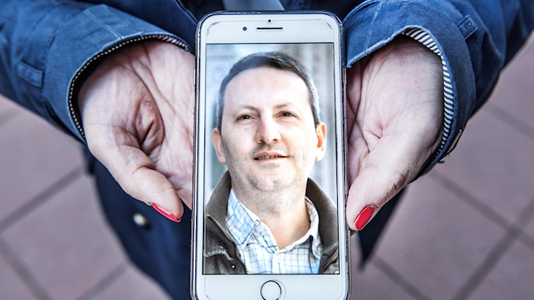 Ahmadreza Djalali's wife holds a phone featuring her husband's picture.
