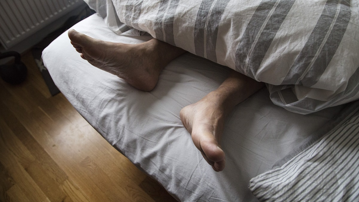 Feet sticking out under a duvet in a bed.