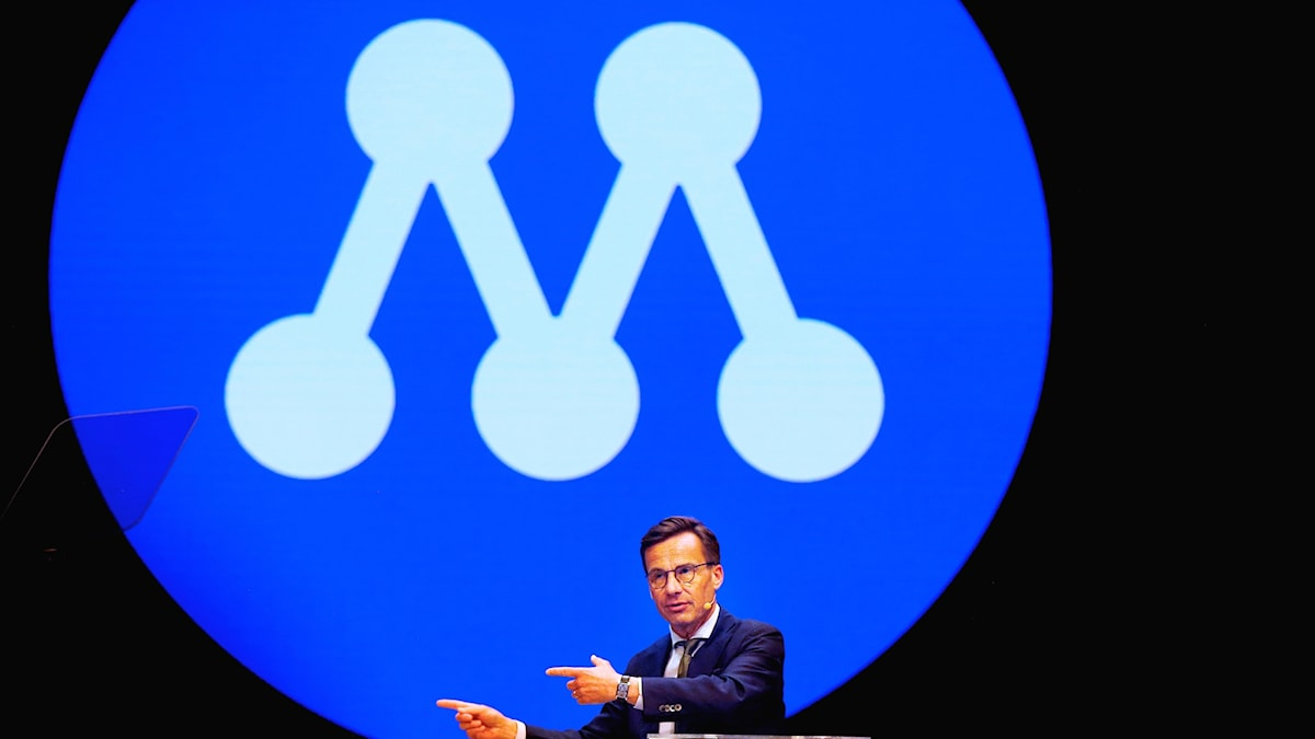 A large stylised letter M as the backdrop to a man talking on a stage