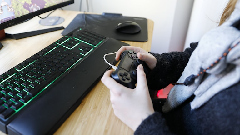 Someone playing a computer game. The face is not visible.
