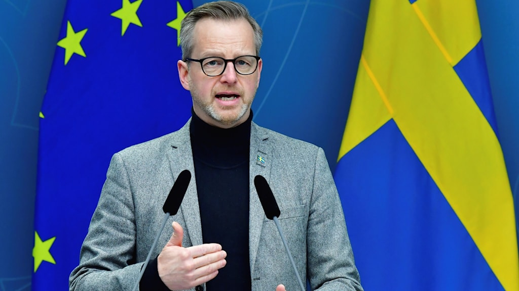 Minister Damberg stands in front of an EU and Swedish flag, talking at a press conference.