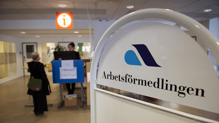 Sign from the Public Employment Agency, Arbetsförmedlingen, with some job seekers in the background.