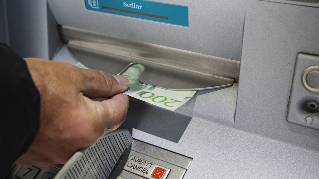 Close-up of hand taking money out of a cash machine.