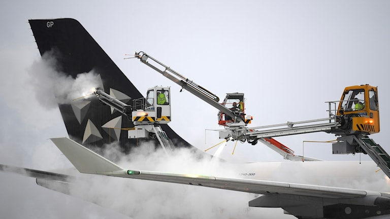 Airplane wing being cleared of snow.