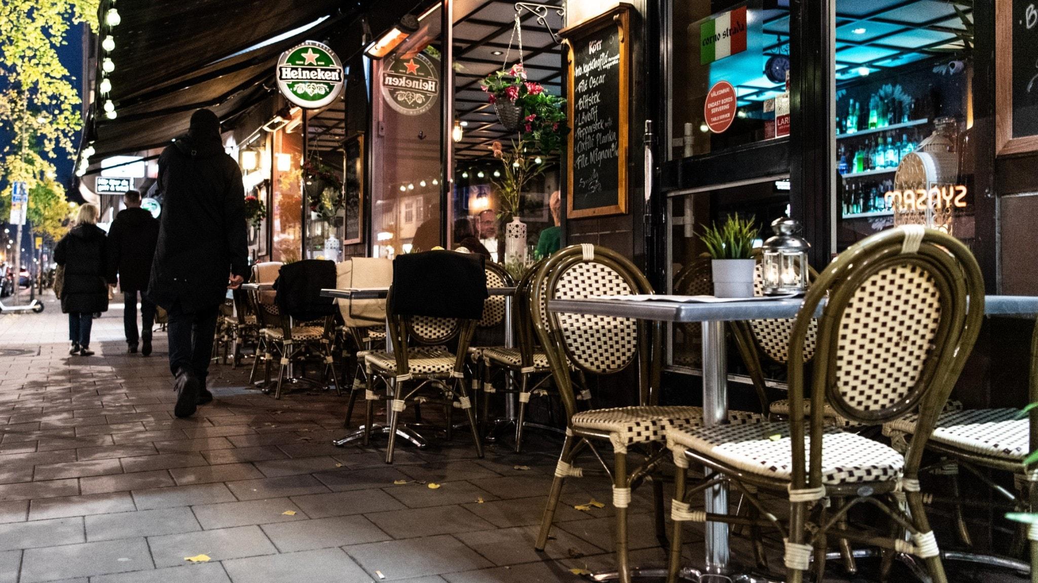 Sidewalk seating at a bar at night.