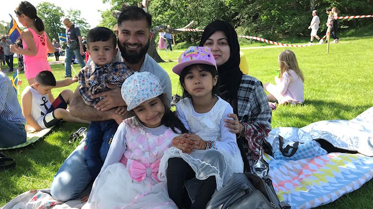Familjen Irfani på en filt i gröngräset