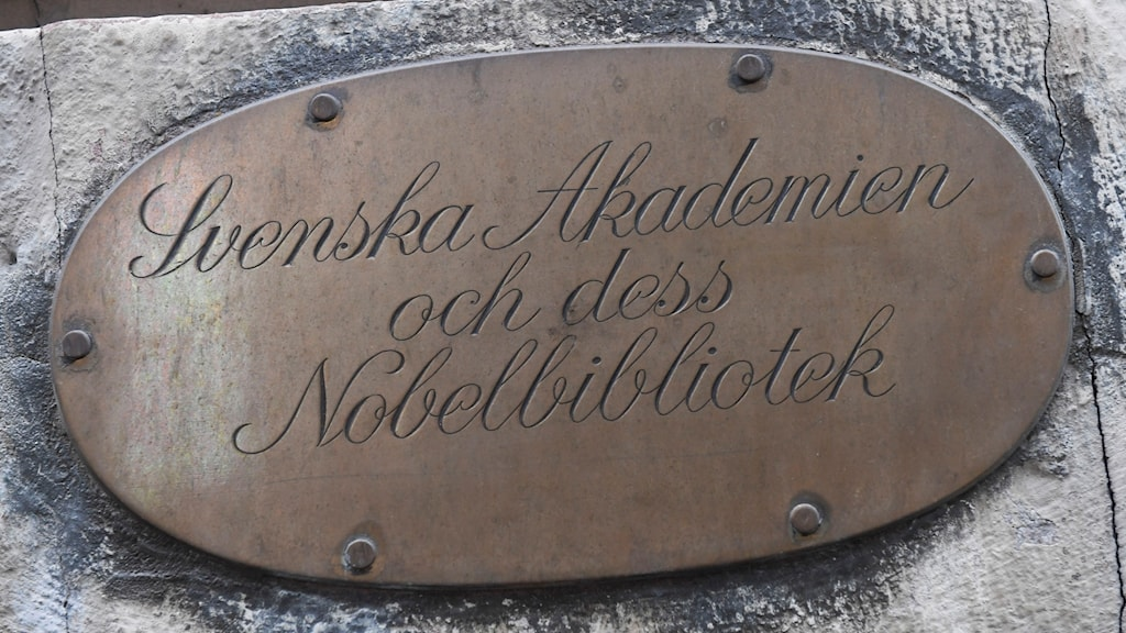 A metal sign on a stone wall.