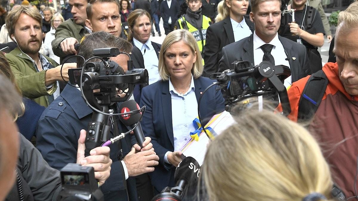 Blond woman carrying a thick pile of papers in a scrum of reporters, microphones and cameras.