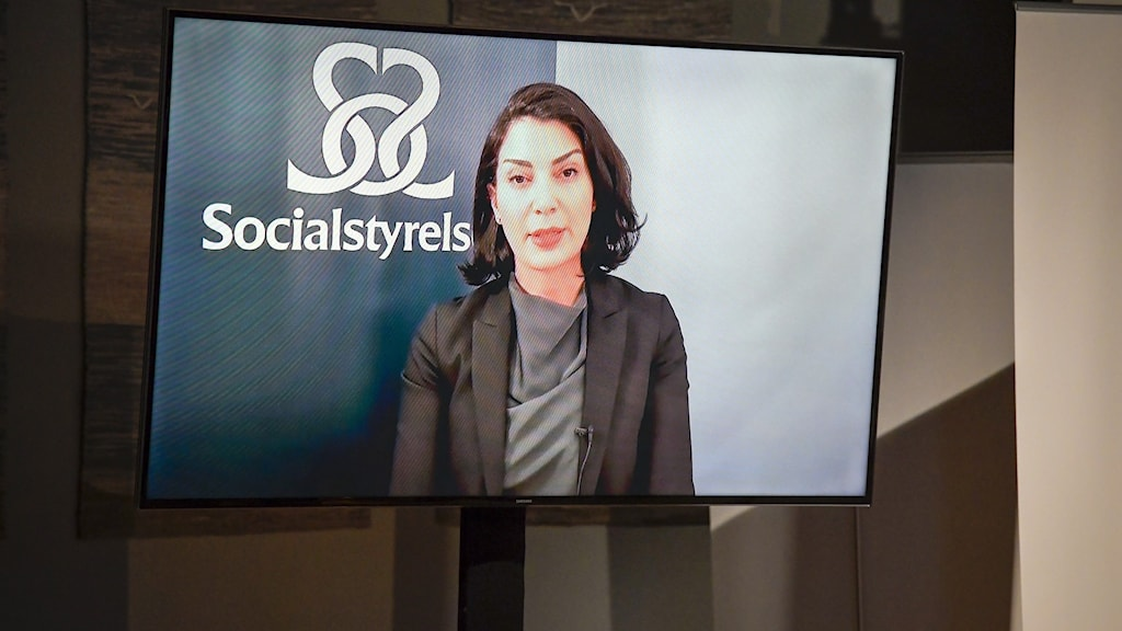 A woman on a large TV screen.