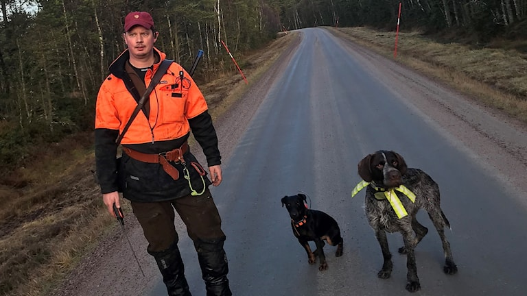 Mattias Wahle standing on a road with two hunting dogs.