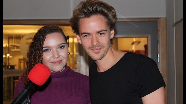 Anton Zetterholm och Jill Svensson står framför en mikrofon.