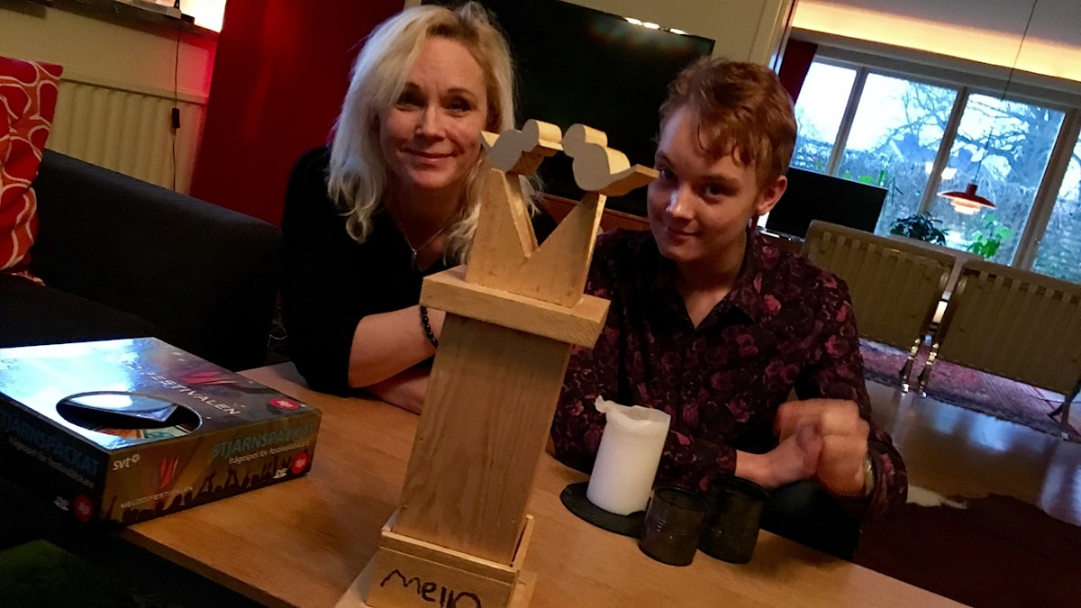 Annelie och Olle Rydqvist sitter i soffan med egentillverkad mello-statyett framför sig.