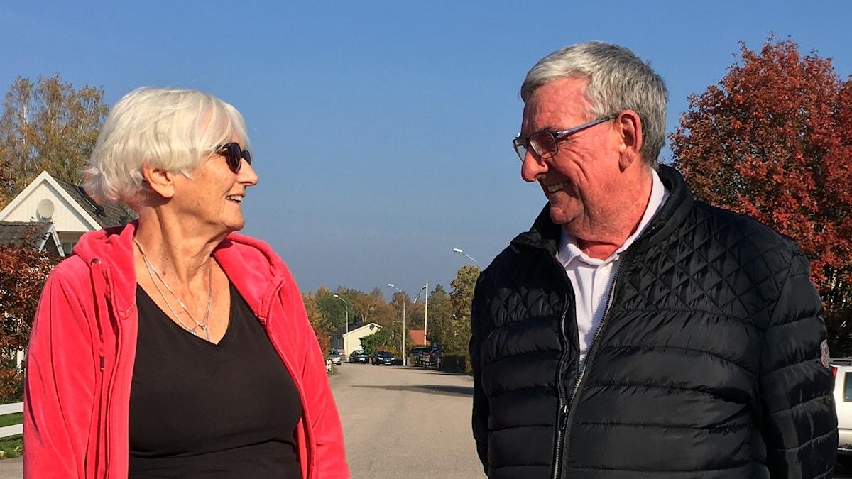 Två äldre personer står och tittar på varandra på en höstig gata
