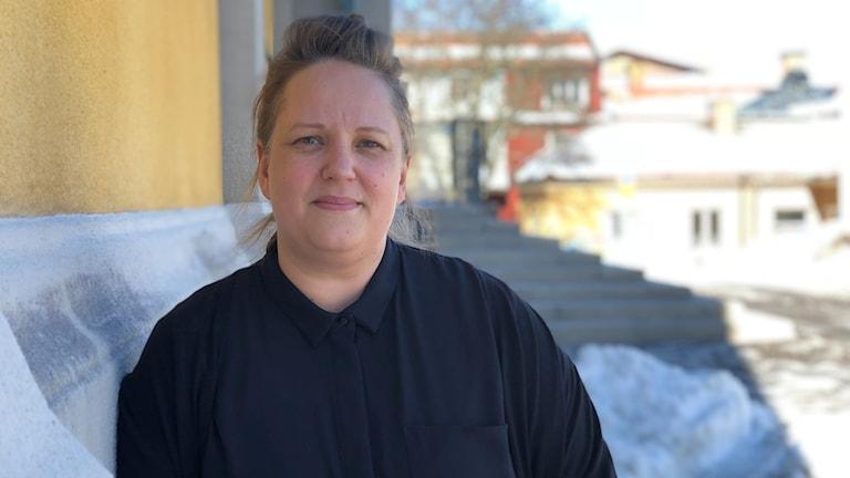 P4 Dalarnas medarbetare Linda Zinderland står lutad mot en husvägg.
