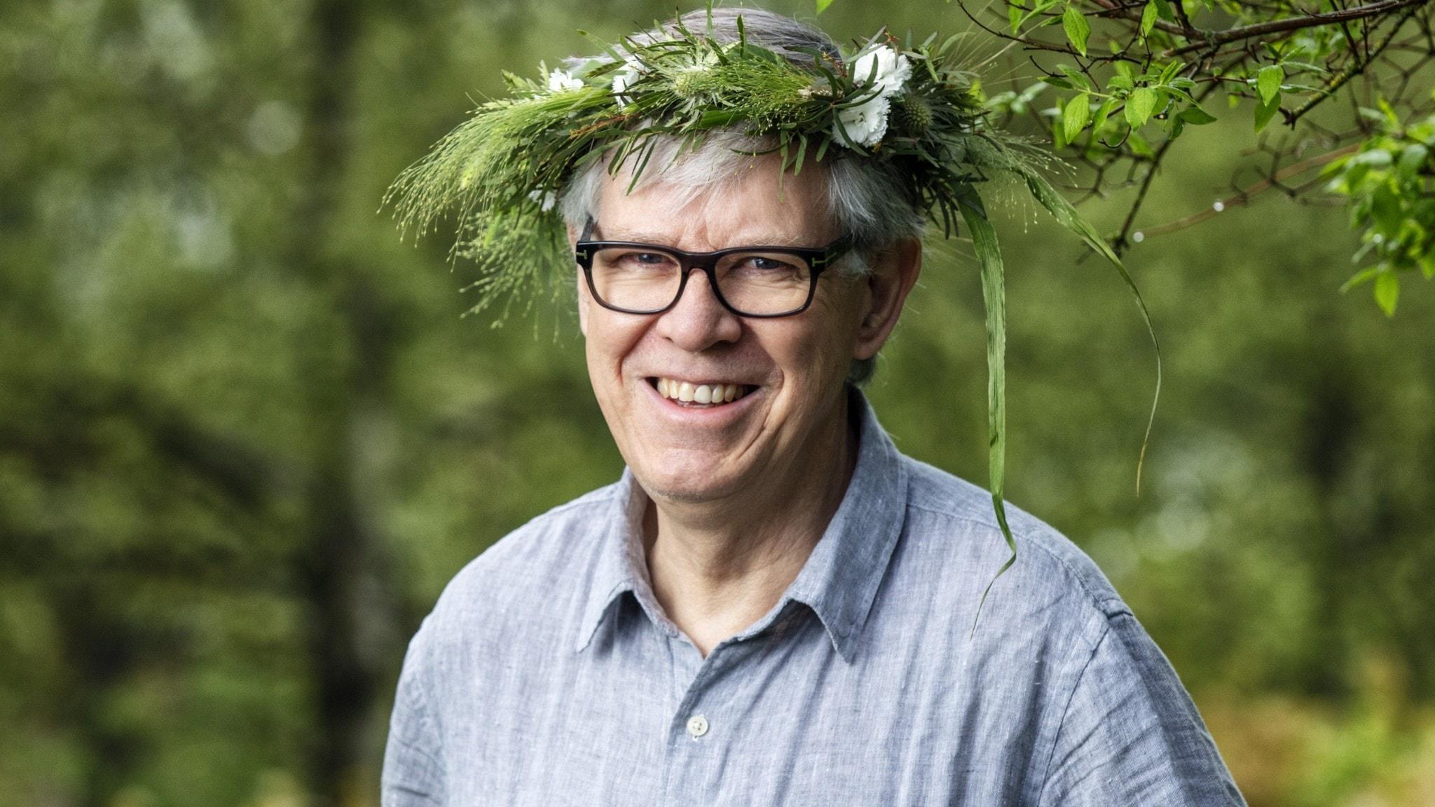 Henrik Ekman med en blomsterkrans på huvudet.