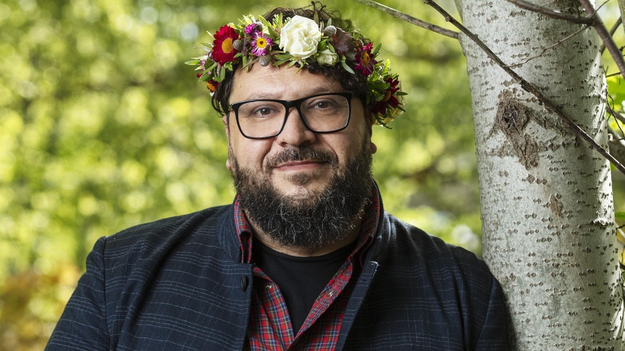 Goran Kapetanović i blomsterkrans, lutar sig mot ett träd.