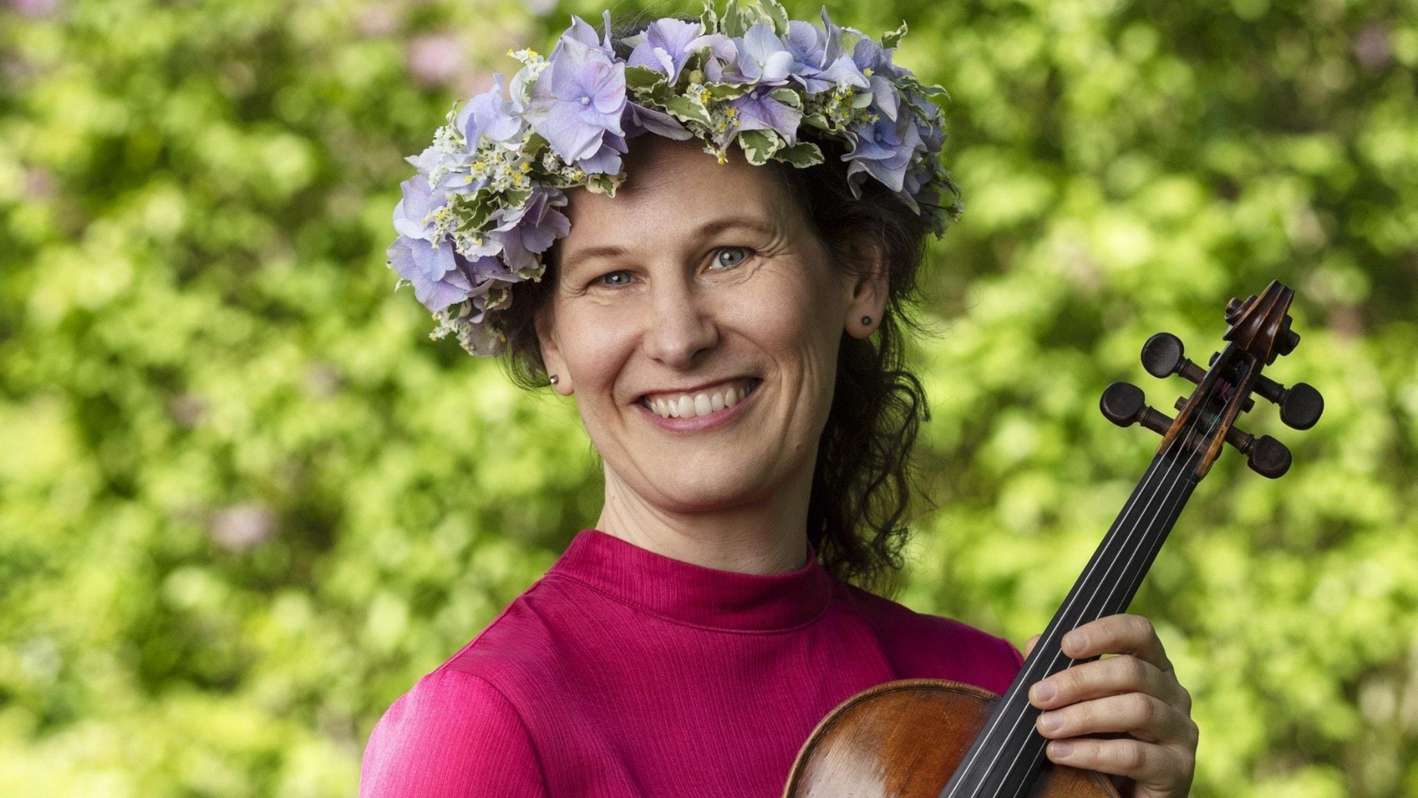 Malin Broman i blomsterkrans och med en fiol i famnen.