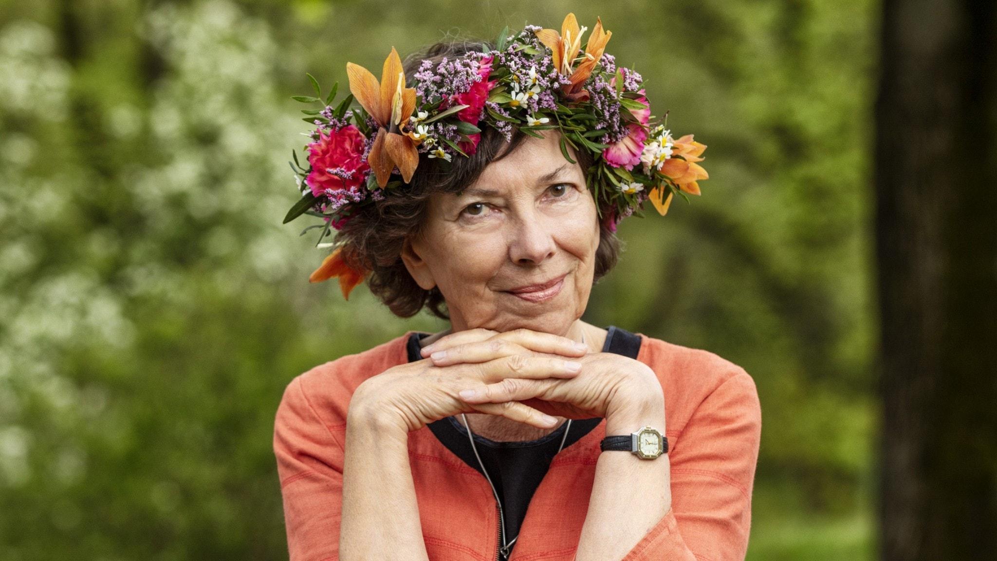 Nina Burton i blomsterkrans, hakan vilar mot hennes knäppta händer.
