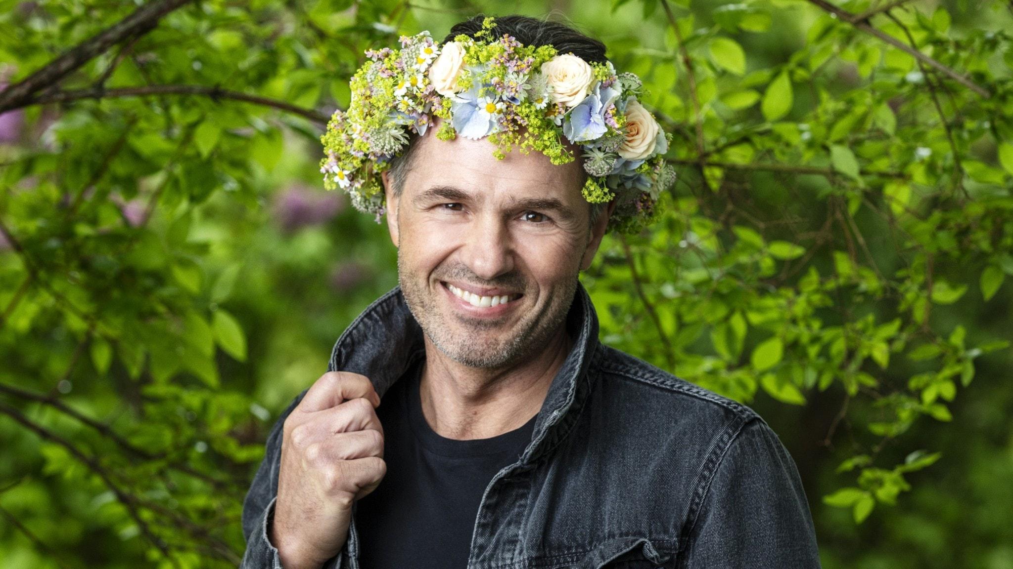 Peter Jöback i blomsterkrans, håller i kragen på jacken med ena handen.