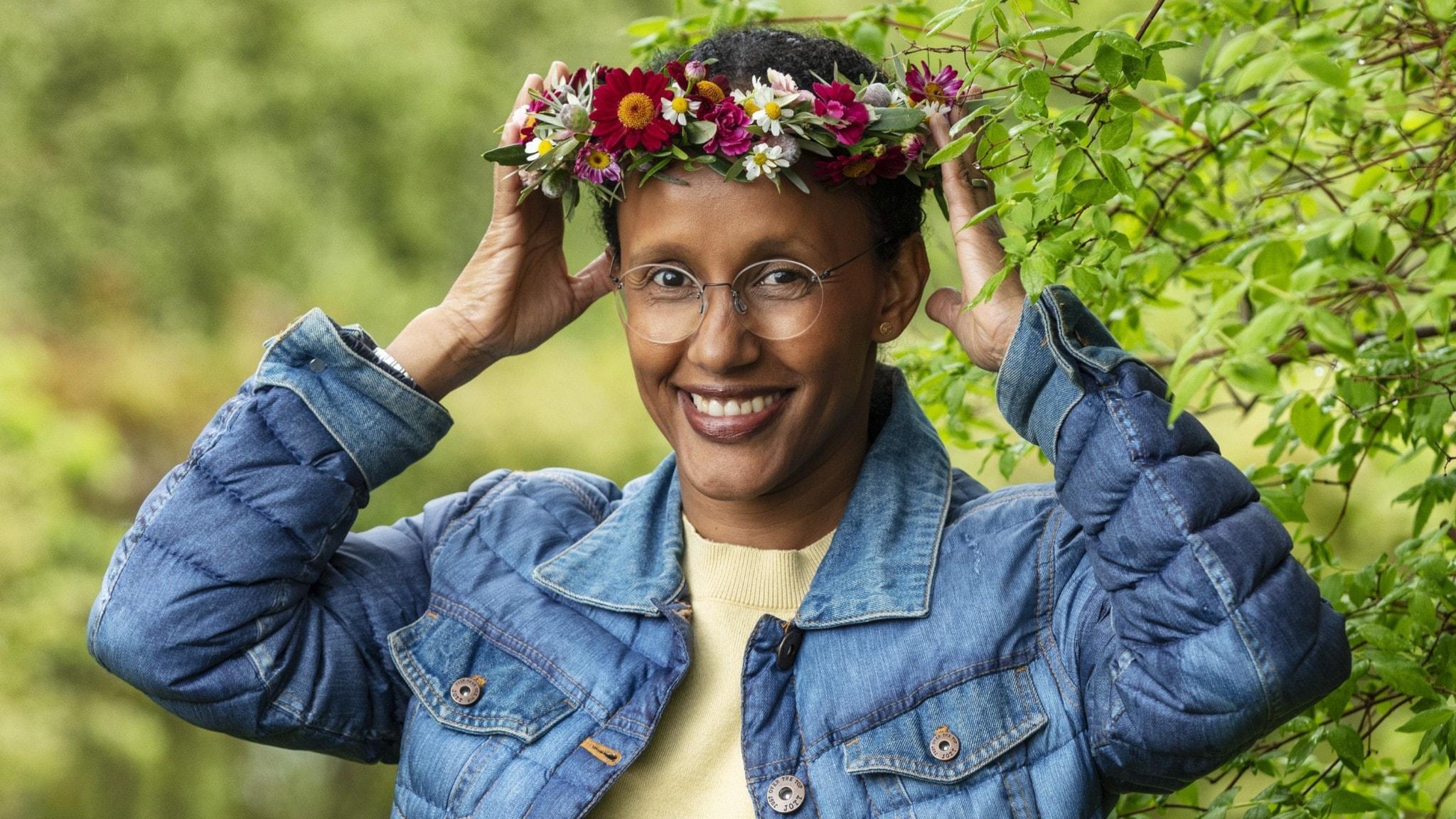 Hanna Wallensteen i blomsterkrans, med händerna på varsin sida om kransen