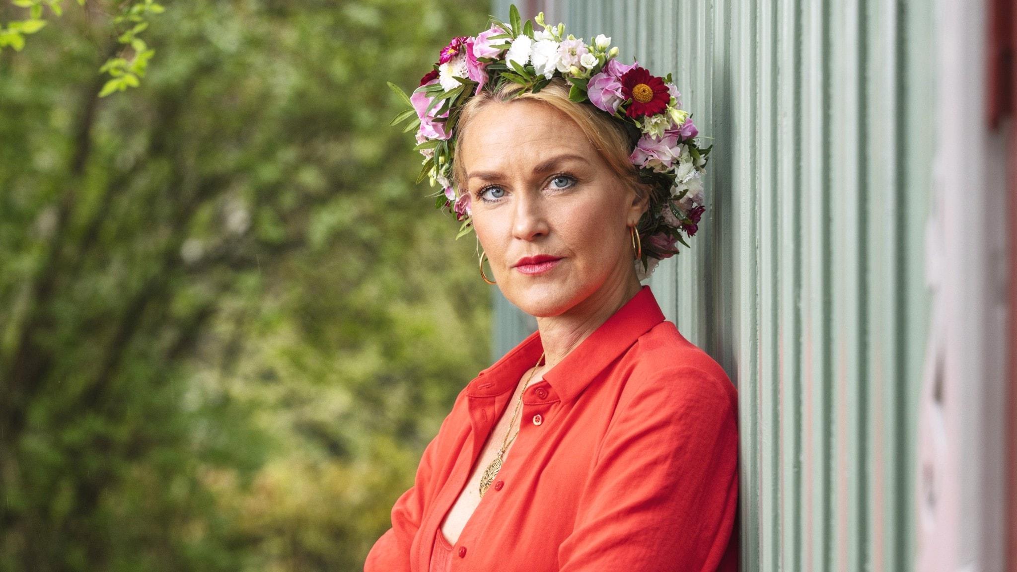 Olga Persson med blomsterkrans på huvudet, lutar sig mot en vägg.