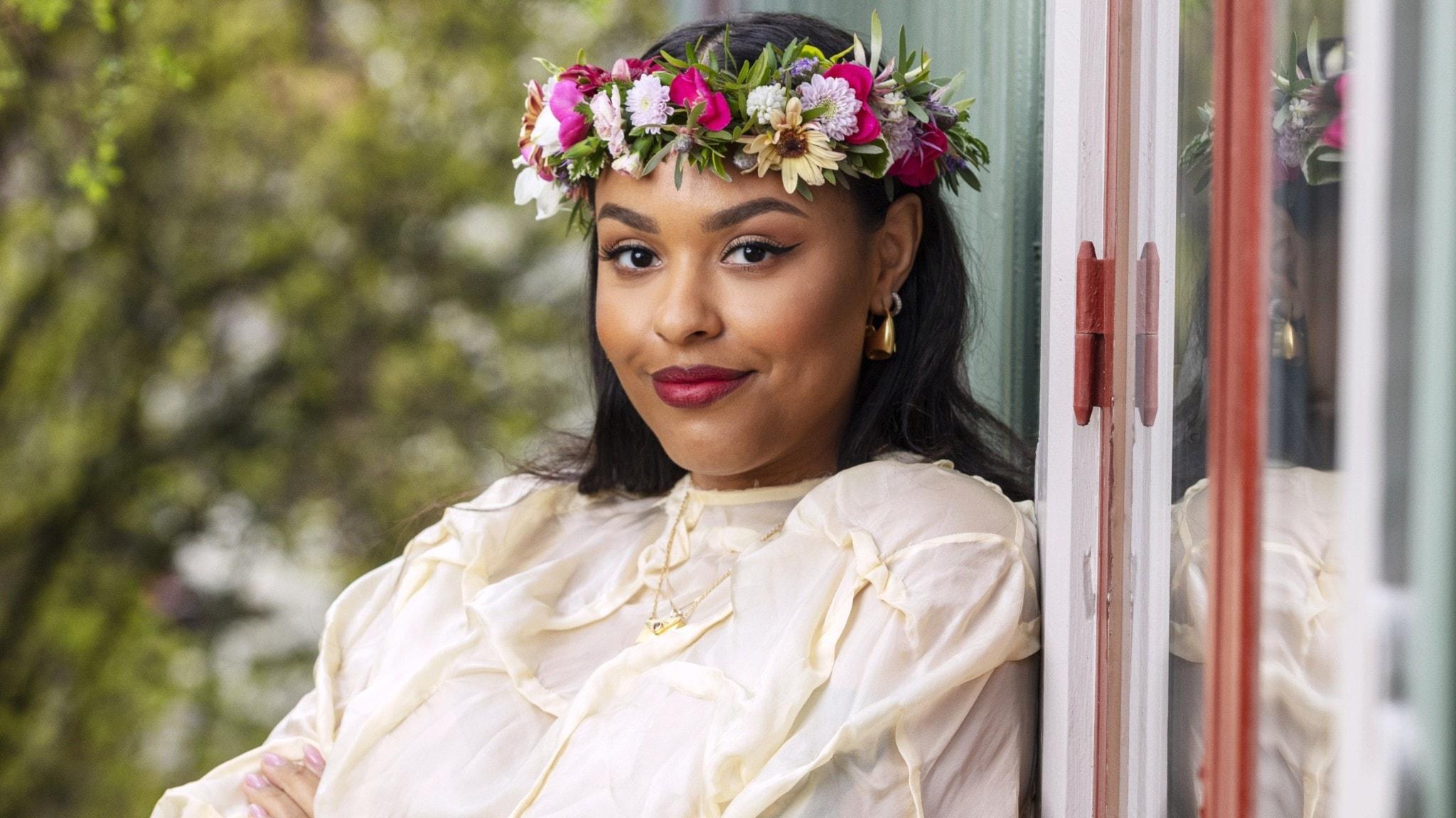 Amie Bramme Sey med blomsterkrans i håret, står och lutar sig mot en husvägg.
