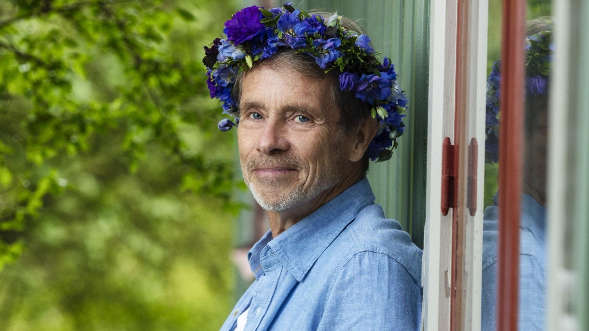 Jacob Hård af Segerstad i blomsterkrans lutar sig mot en vägg.