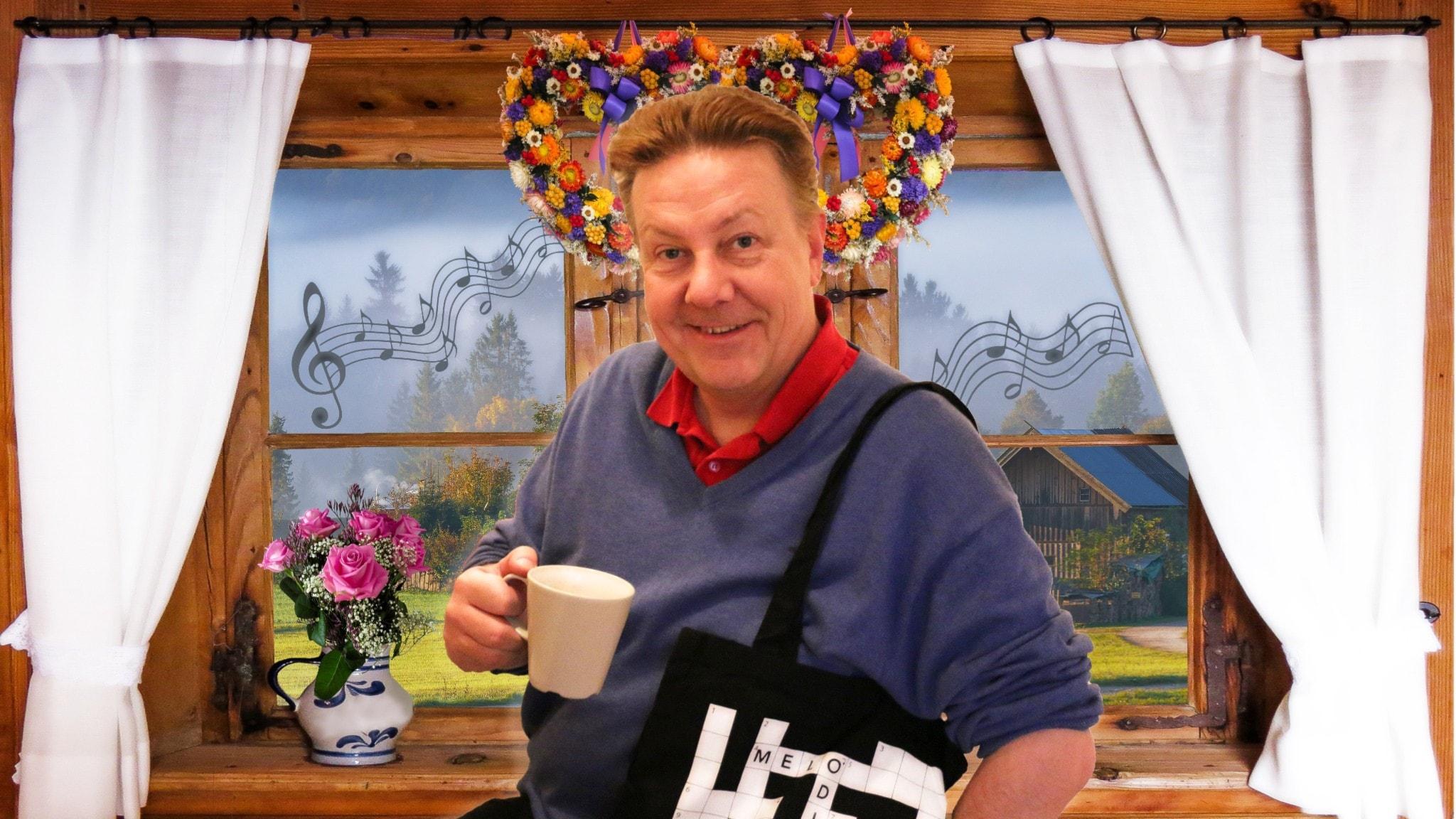 Anders Eldeman i mysig miljö på landet där man anar en ladugård genom fönstret. I handen håller han en kopp kaffe.