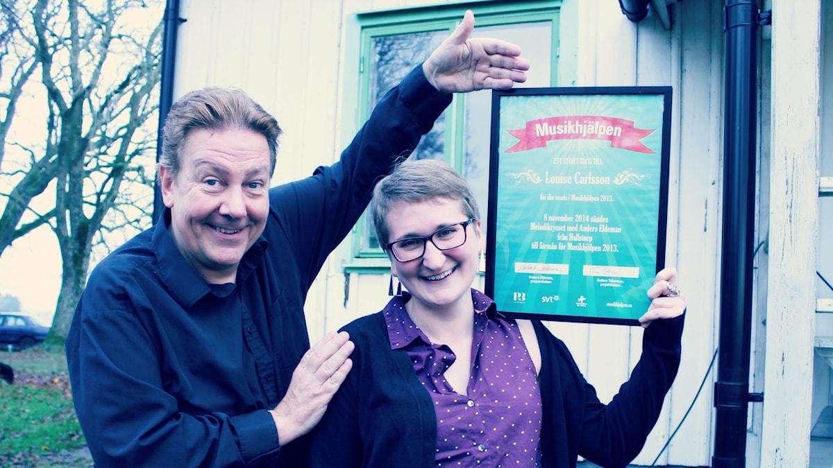 Louise Carlsson får ett diplom av Anders Eldeman för vinsten i musikhjälpentävlingen. Foto: Ronnie Ritterland / Sveriges Radio