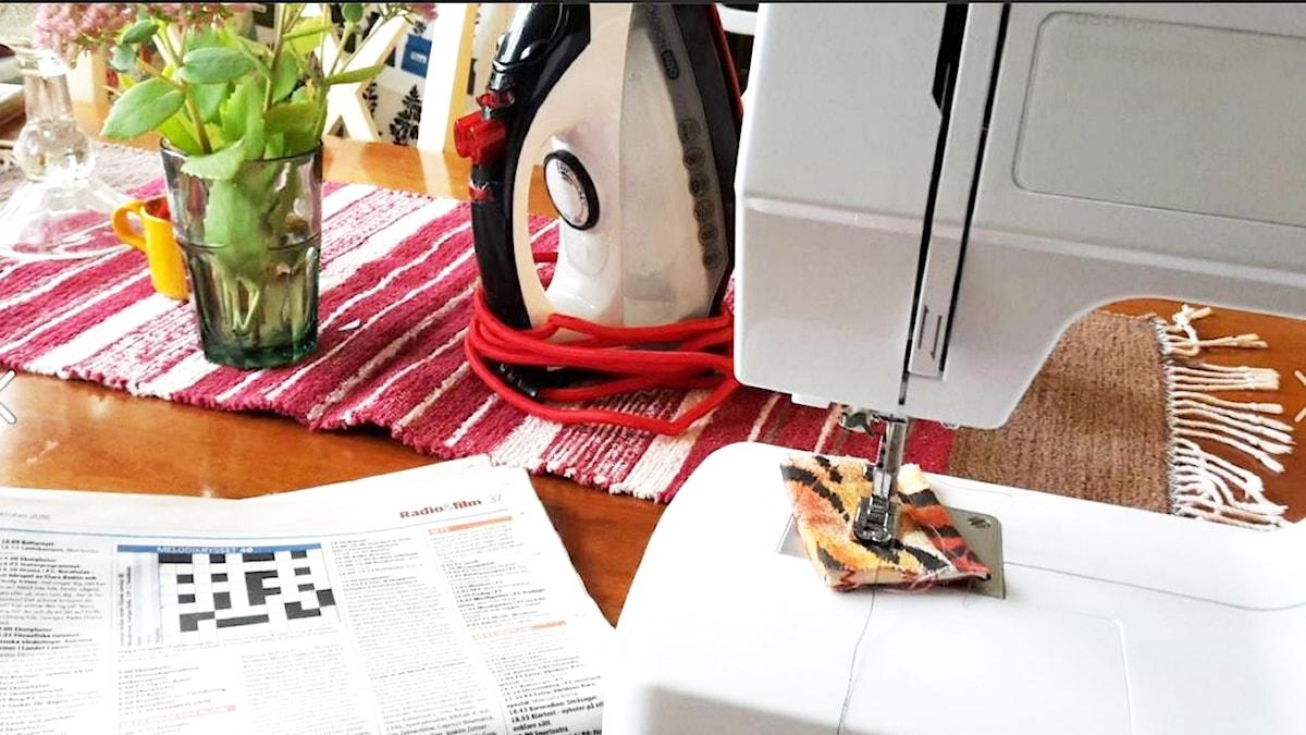 Bild på tidning med kryss en symaskin och ett strykjärn.