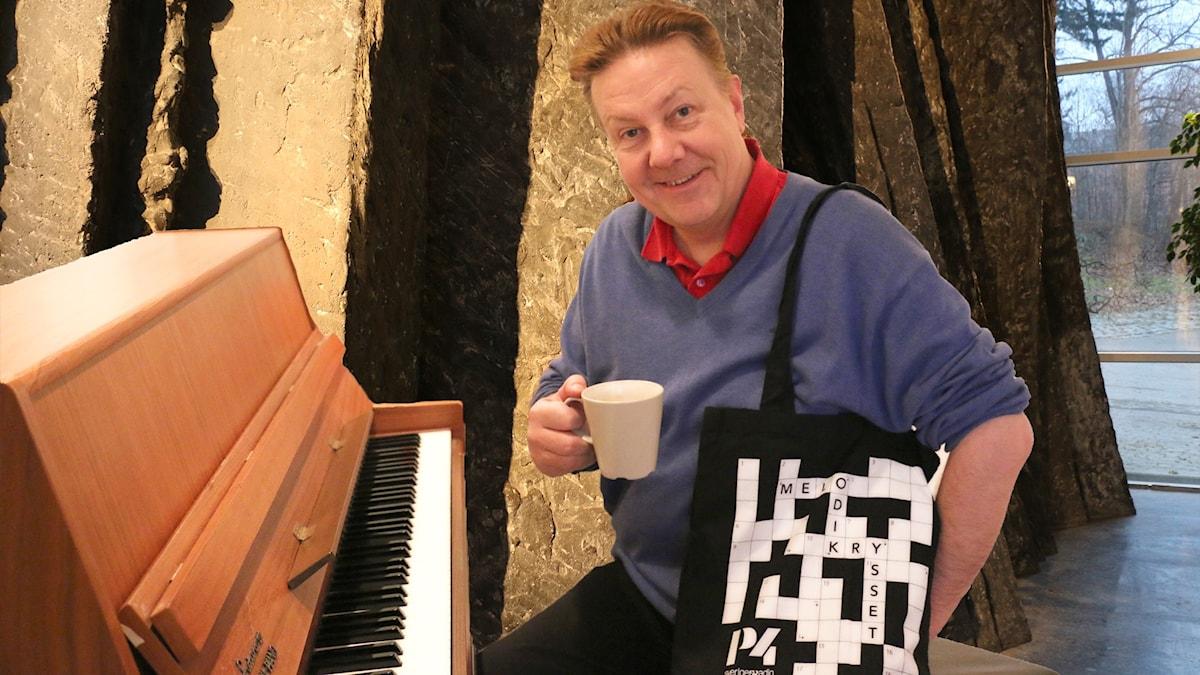 Anders Eldeman sitter vid ett piano med en kopp kaffe.